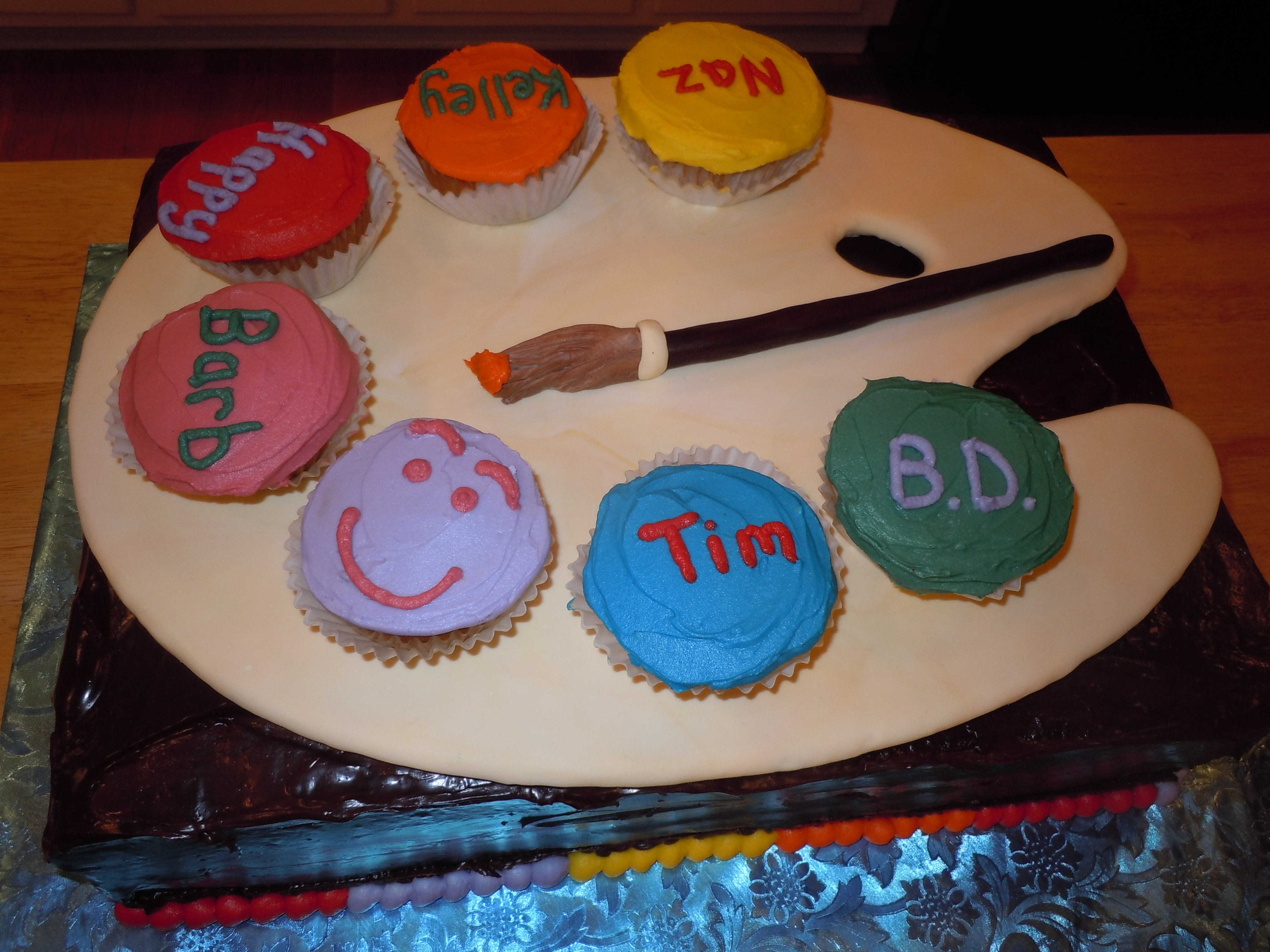Edible art: gumpaste palette board and paint brush. Colorful cupcakes in a rainbow of colors.