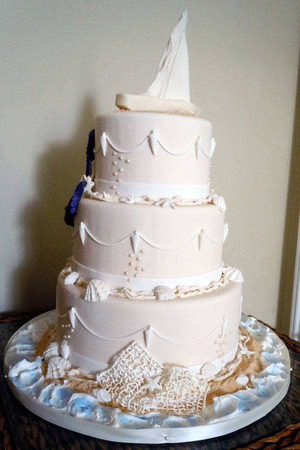 Nautical wedding cake with modeling chocolate boat cake topper, Sugarveil fishing net, fondant shells and lines.
