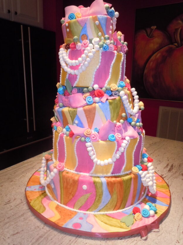 Whimsical topsy-turvy cake with ribbon roses, pearls and bows.