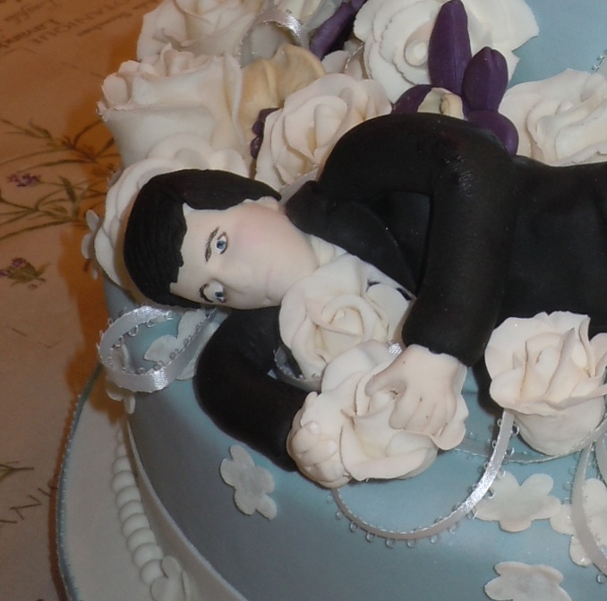 Terrified groom clutching a flower, both made out of gumpaste and fondant.