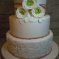 Wedding cake with edible lace details to match the fabric in the bride's gown; gumpaste Ranunculus to match her bouquet.
