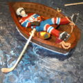 Edible sugar art hockey player sleeping (passed out) in a chocolate row boat.