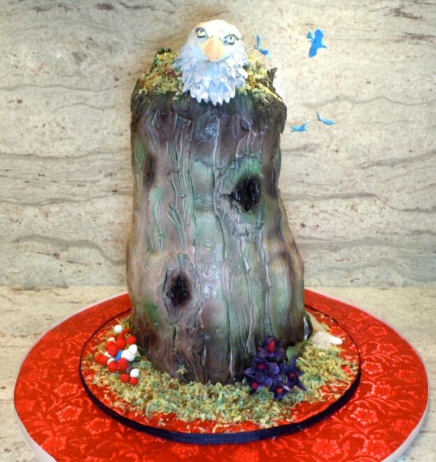 The bald eagle sits atop a tree stump that is filled with red, white and blue cake. All of the elements are edible.